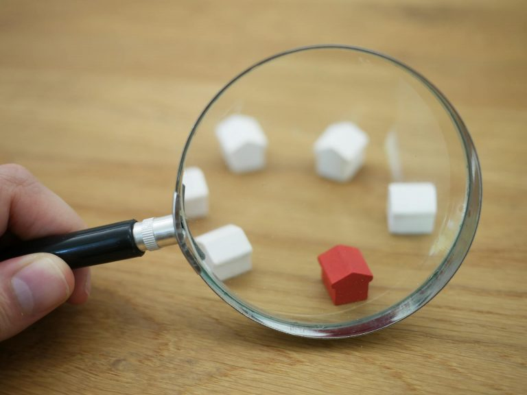 A hand holding magnifier over small toy houses