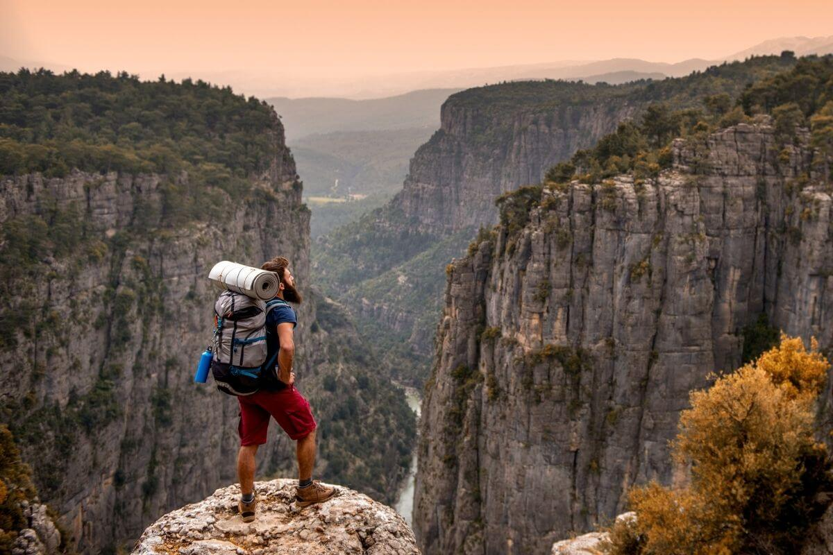 A scene where a backpacker stands in front of Tazi Canyon